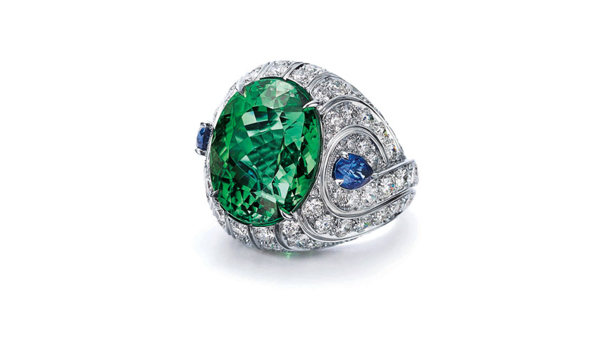 Ring of an oval cut green tourmaline with two pear shaped blue sapphires and round diamonds